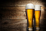 Two beer glass on a table and wooden background