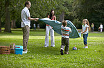 Family shaking out picnic blanket in park