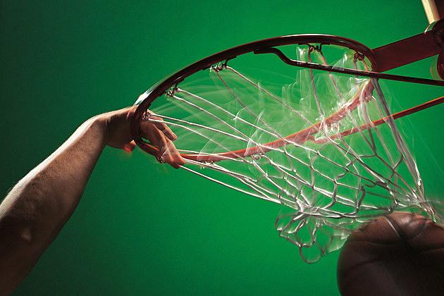 Player slam dunking basketball through hoop